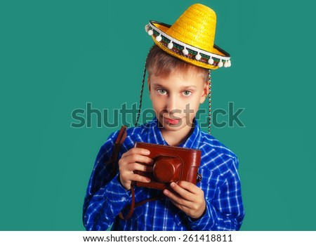 Funny little child traveler with vintage camera, sombrero and suitcase. Travel and vacation concept. (soft focus, filtered) - stock photo