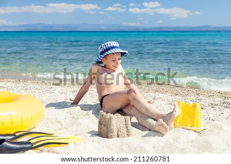 Funny little child with a panama sitting on beach with swimming accessories and relaxing - stock photo