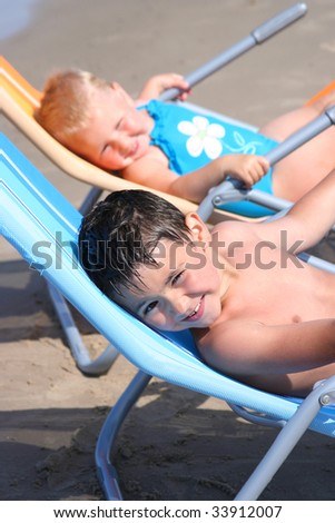 funny little couple relaxing on the beach - stock photo