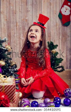 Funny little fashion girl celebrating Christmas surrounded by gifts and Christmas ornaments - stock photo
