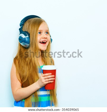 Funny little female model with headphones  standing against white background with red coffee cup, glass. Long blonde hair. - stock photo