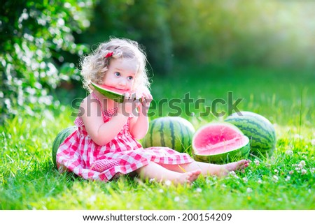 Funny little girl, adorable toddler with curly hair wearing a red dress, eating watermelon, healthy fruit snack, playing in a sunny garden on a hot summer day - stock photo