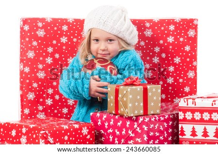 Funny little girl around christmas boxes holding red ball for christmas tree - stock photo
