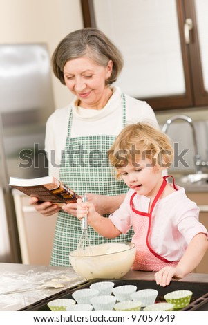 Funny little girl baking cupcake with grandmother hold whisk - stock photo