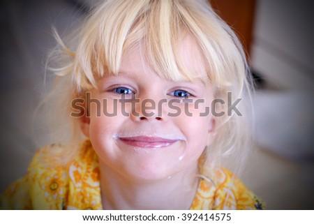 Funny little girl drinking milk. Healthy breakfast. - stock photo