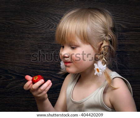 Funny little girl eating a strawberry. Portrait, face close. Blond hair, pigtails. Strawberries ripe, red. Girl grubby and rather - stock photo