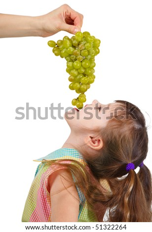 Funny little girl eating grapes from the mother's hands - stock photo