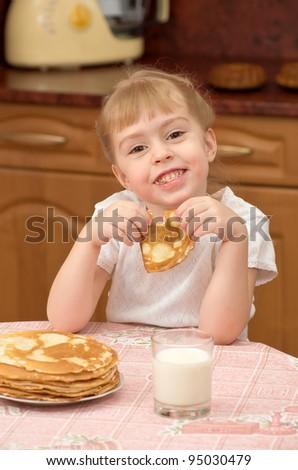 Funny little girl eats pancakes - stock photo