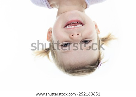 funny little girl hanging upside down on white - stock photo