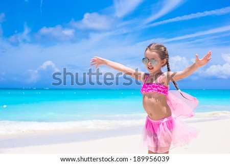 Funny little girl have fun on beach summer vacation - stock photo