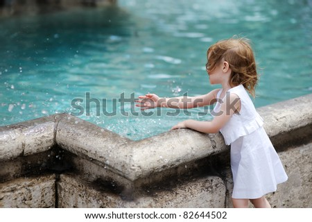 Funny little girl having fun by a city fountain - stock photo