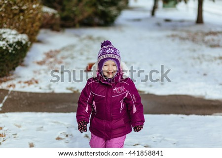 Funny little girl having fun in beautiful winter park during - stock photo