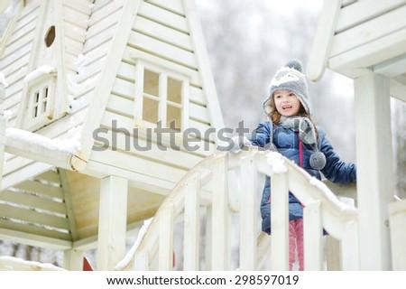 Funny little girl having fun in beautiful winter park during snowfall - stock photo