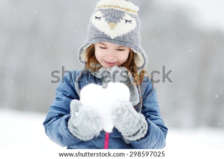 Funny little girl holding snow heart in beautiful winter park during snowfall - stock photo