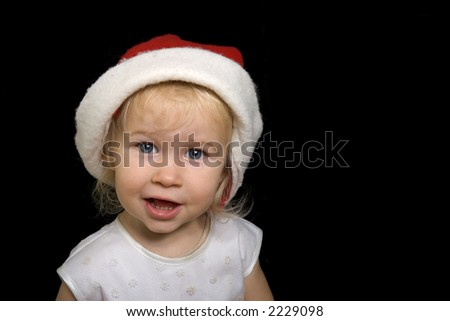 funny little girl in big christmas Santa red hat, isolated on black - stock photo