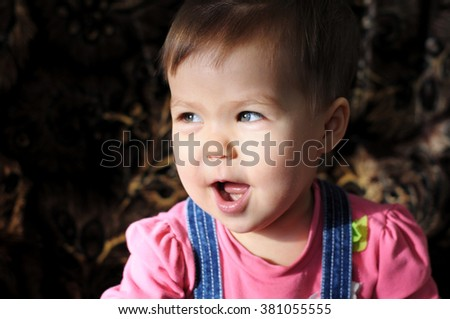 Funny little girl in dark background looking away - stock photo