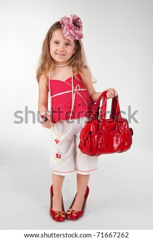 Funny little girl in her mother's accessories and shoes over the gray background - stock photo