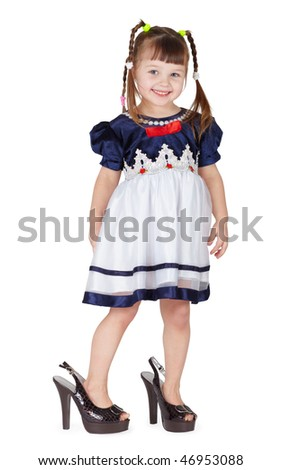 Funny little girl in her mother's big shoes isolated on white background - stock photo