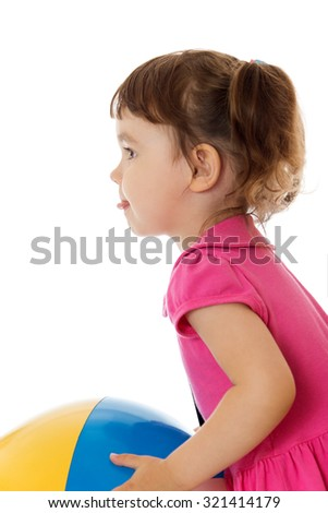 Funny little girl in pink dress with hands throws the ball. . The girl turned sideways to the camera , it shows the language-Isolated on white background - stock photo