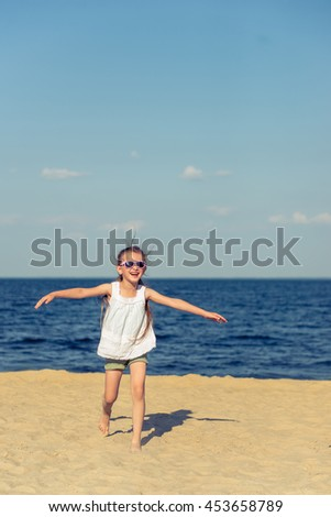 Funny little girl in sun glasses is running and smiling while playing on the sunny seaside - stock photo