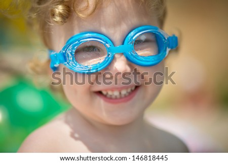 Funny little girl in water glasses portrait - stock photo