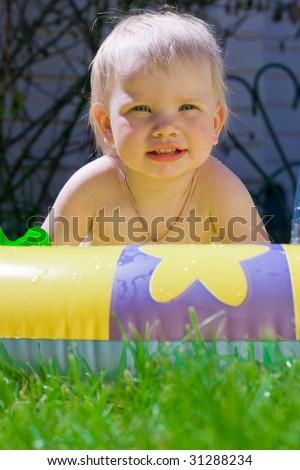 Funny little girl in yellow pool - stock photo