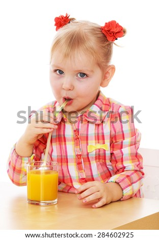 Funny little girl is drinking orange juice through a straw while sitting at table- isolated on white background - stock photo