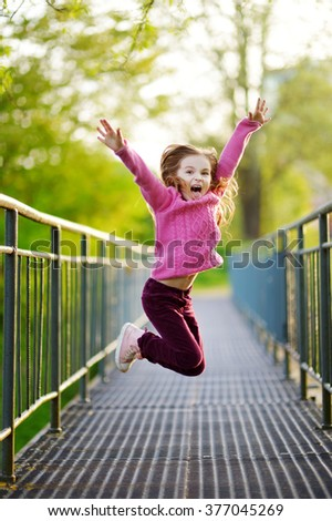 Funny little girl jumping with joy and happiness outdoors on beautiful summer day - stock photo
