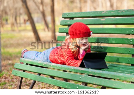 Funny little girl learning with tablet pc in the park. - stock photo