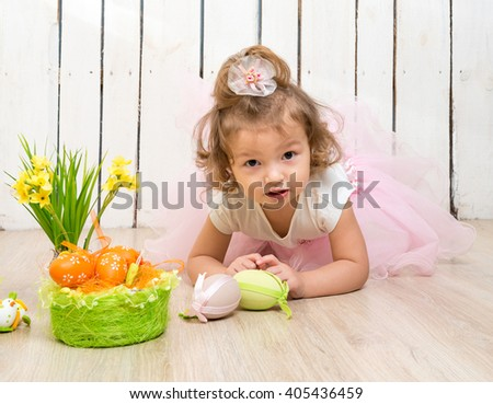 funny little girl lying on the floor with easter decorations and looking at camera