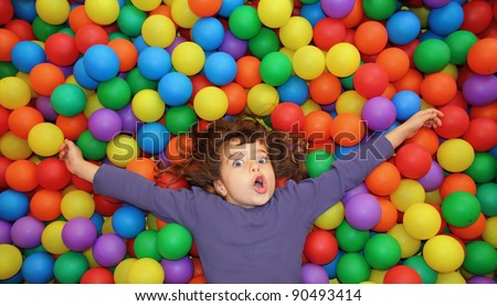 funny little girl lying over colorful balls in the park gesturing happy