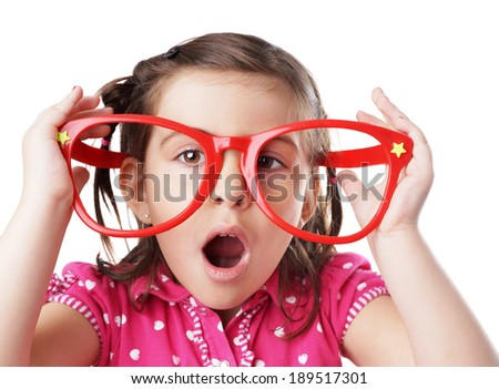 Funny little girl making face with big red plastic glasses - stock photo