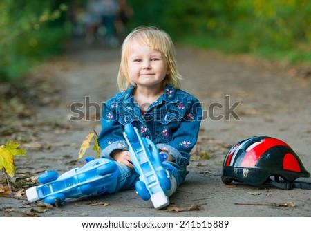 Funny little girl on roller skates sitting on road in the park - stock photo