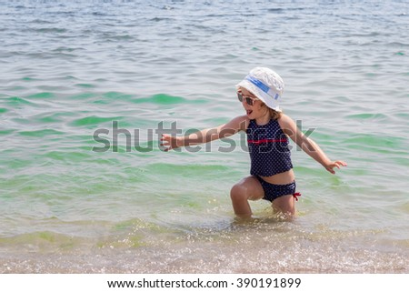 Funny little girl on the beach, selective focus.