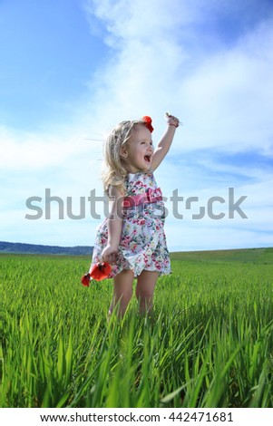 Funny little girl outdoors opening his mouth waving hand. Standing in green field on background of clouds