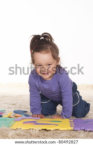funny little girl playing on a carpet