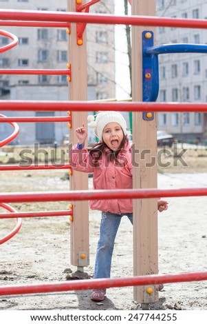 Funny little girl playing on outdoor playground equipment - stock photo