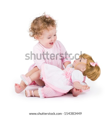 Funny little girl playing with a beautiful doll - stock photo