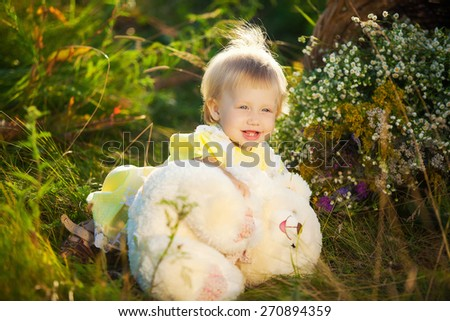 Funny little girl playing with toy teddy bear outdoors. Cute little child on the meadow in summer day - stock photo
