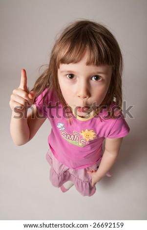Funny little girl raising one finger