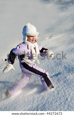 Funny little girl running in the snow - stock photo