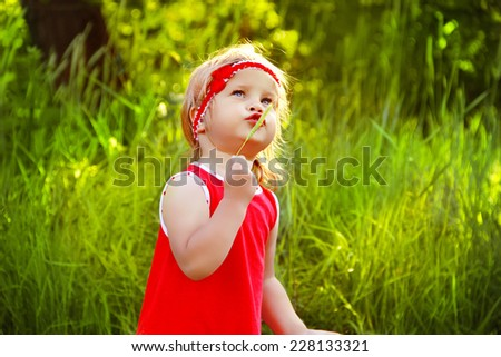 Funny little girl singing and walking on green grass, outdoor portrait - stock photo