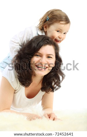 Funny little girl sits on mother which lying on white fluffy rug
