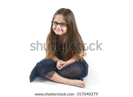 Funny little girl sitting on the floor. Studio photography on a white background. Age of child 4 years. - stock photo