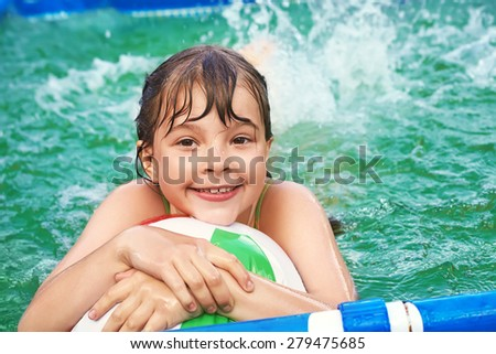 funny little girl splashing in the water in swimming pool. child outdoors - stock photo