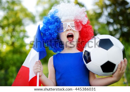 Funny little girl supporting and cheering her national football team during soccer championship - stock photo