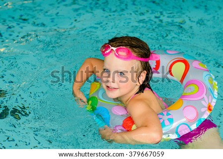 Funny little girl swimming in a pool in colorful life preserver - stock photo