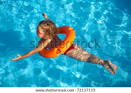 Funny little girl swims in a pool in an orange life preserver - stock photo