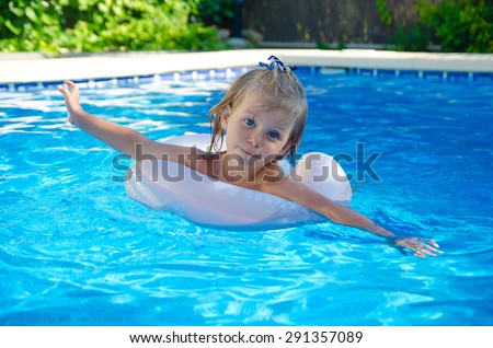 Funny little girl swims in a pool in the life preserver  - stock photo