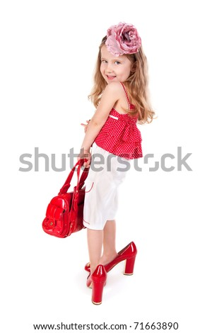Funny little girl trying on her mother's accessories and shoes - stock photo